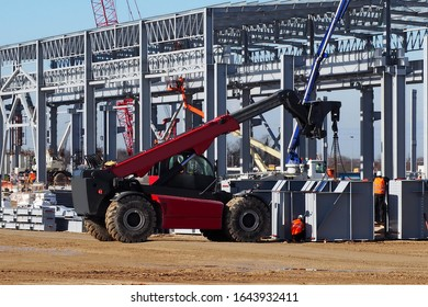 Telescopic handler at work in a large construction site. Intense building activity on background