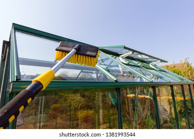 Telescopic water fed pole being used to clean the roof of a greenhouse