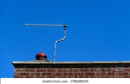 A television aerian on a rooftop against a deep blue sky