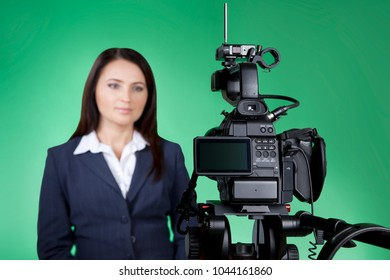 Television announcer isolated on green background in blur. A TV host presents news. Looking at the camera