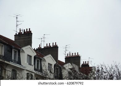 Television antennas and chimneys on roof. TV antennas. Red chimneys. White facade building. Parts of slate roof.