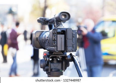 Television camera in the focus, blurred people in the background