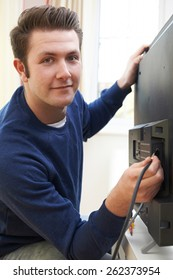 Television Engineer Installing New Television At Home