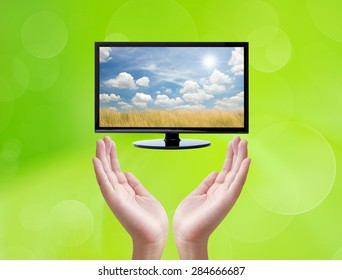Television and hand on green background
