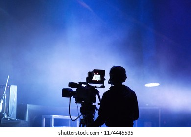 Television live streaming cameraman during a concert. Live action. Blues tone