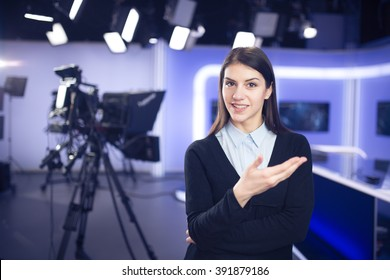 Television presenter recording in news studio.Female journalist anchor presenting business report,recording in television studio,showing hands gesture and talking to the camera..News behind the scenes