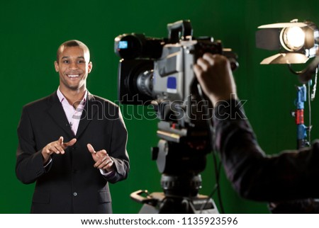 Television presenter in a studio. Foreground television camera and camera operator's hand. Background green screen curtain and studio light.