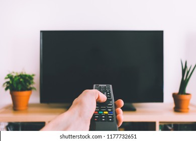 Television with remote control in hand mockup