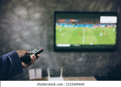 Television remote control in human hands, Football match and remote control