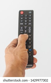 Television remote in hand on white background, Isolate digital electronic remote in hand to on and off television