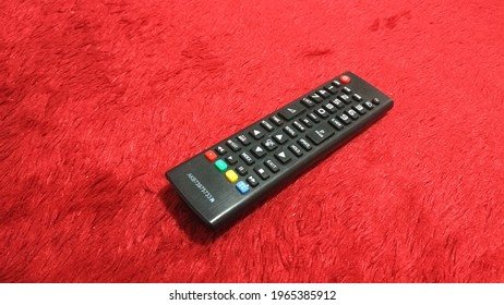 Television remote on the red velvet carpet  - Shutterstock ID 1965385912