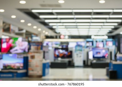 Television Smart TVs 4K Ultra HD home entertainment display on shelves in eletronic department retail store abstract blur defocused background