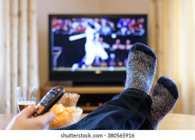 Television, TV watching (baseball match) with feet on table eating snacks and drinking beer - stock photo