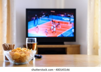 Television, TV watching (volleyball match) with snacks and alcohol on table - stock photo