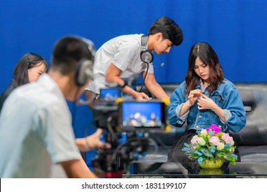 Television video camera recording interview in broadcast studio. Asian woman clipping tie-clip microphone and Professional cameraman with headphones looking video camera viewfinder. Selective focus