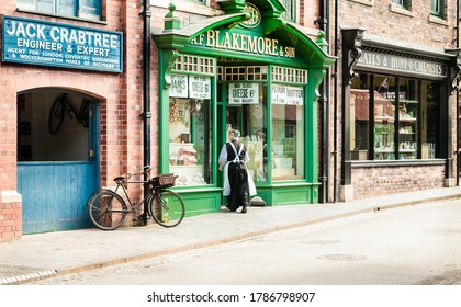 Telford, England.- July 9th 2014:  woman dressed as Victorian shopkeeper entering a greengrocers shop at the famous tourist attraction the working museum in blists hill victorian town