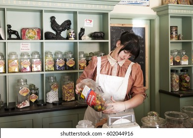 Telford, England.- July 9th 2014 : Young female tipping candy out on shop scales in Victorian Confectioner Old Sweet Shop. Blists Hill Victorian Town Telford, Shropshire, England.