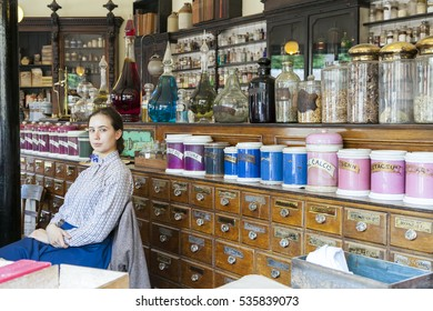 Telford, England.- July 9th 2014:Young female sales assistant sitting down in Victorian Chemist/ Pharmacy, at Blists Hill Victorian Town museum, England UK