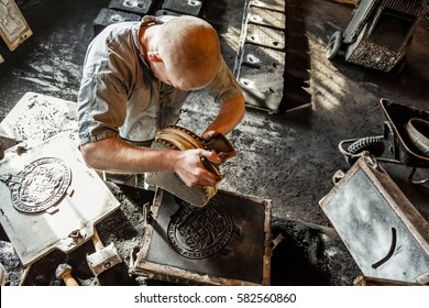 TELFORD, UK - CIRCA 2013: A man makes a mold for pouring cast iron at Blists Hill Victorian Museum in Ironbridge, UK
