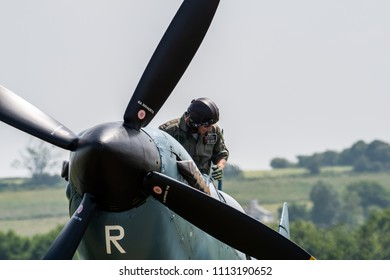 teLFORD, UK, JUNE 10, 2018 - A photograph documenting the pilot of a Supermarine Spitfire climbs down from his cockpit after landing at the airfield at RAF Cosford