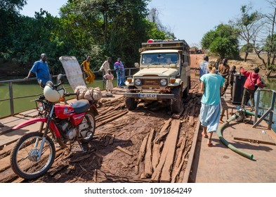 Telimele, Guinea - December 21, 2013: Motorbike, 4x4 vehicle, people crossing river on simple raft, Fouta Djallon