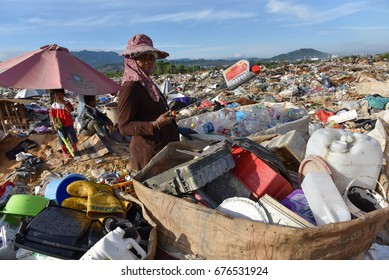 Telipok Kota Kinabalu Sabah Malaysia - July 08, 2017 : A Mother is sorting out things that can be used for sale and are being observed by two boys, her son