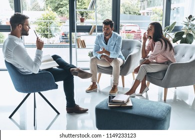 Tell me about your feelings. Young married couple talking while sitting on the therapy session with psychologist