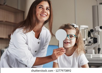 Tell me what you see on the board. Little girl tries new blue glasses in ophthalmologic office with female doctor.