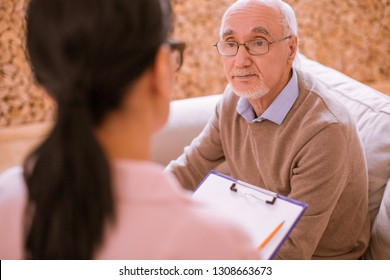 Tell the truth. Kind pensioner sitting opposite his interlocutor and answering on questions