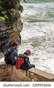TELLARO, LIGURIA, ITALY, APRIL 4, 2018: Two young hiker, a boy and a girl, resting sitting on the sea cliff after a walk on the coast of Liguria, Cinque Terre, Mediterranean Sea, Italy.