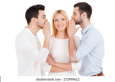 Telling fresh gossips. Two young man telling gossips to beautiful woman standing between them and against white background