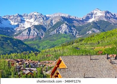 Telluride city panorama with snow mountain peaks and forestry hillsides. Beautiful town at high altitude on a sunny day in Colorado, USA.