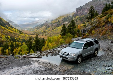 Telluride, Colorado, USA - October 05, 2015: On a rainy and misty autumn day, a SUV is driving through a mountain creek on rugged Black Bear Pass trail - the only way to the top of Bridal Veil Falls.