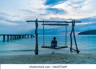 Teluk Keke Beach, Besur, Perhentian Islands, Malaysia; 17-May-2019; a lady enjoying a swing by the sea at sunset, Teluk Keke Beach, Besur, Perhentian Islands, Malaysia