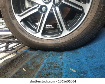 Temanggung, Indonesia, 02 December 2020 car wheels on the blue carpet, dirty, mossy, and wet