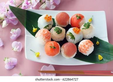 Temarizushi,Japanese cuisines ball-shaped sushi on pink background