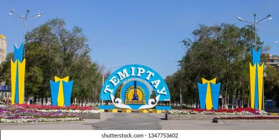 Temirtau, Karaganda/Kazakhstan - September 08, 2017: Avenue with Emblem and Flag of City Temirtau. Entrance from Karaganda Region.