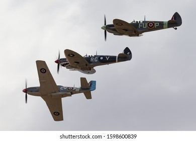 Temora, Australia - November 2, 2013: Commonwealth Aircraft Corporation CA-18 Mustang (North American P-51D Mustang) in flying formation with two Supermarine Spitfires.