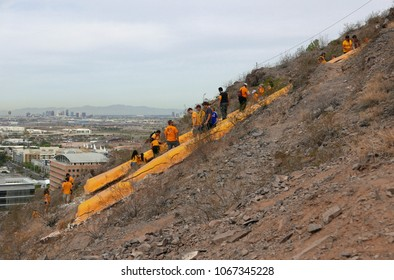 Tempe, Arizona, March 24, 2018: Students painting a giant A on a mountain with the city of Phoenix in the background