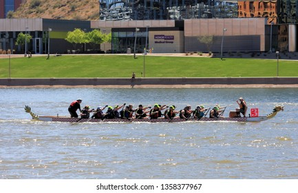Tempe, Arizona / United States - March 30, 2019: Unnamed team races toward the finish line during the Arizona Dragon Boat Festival on Tempe Town Lake in Tempe, Arizona.