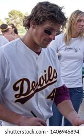 TEMPE, ARIZONA / USA - APRIL 24 2005: ASU Sun Devils star outfielder  #4 Travis Buck signs a baseball at ASU Sun Devils Bobby Winkler Field.