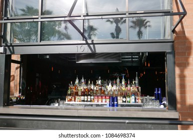Tempe, Arizona, USA - March 24, 2018: Window of a bar with many different bottles of alcohol