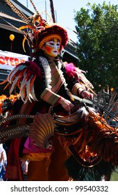 TEMPE, AZ - MARCH 31: An unidentified woman in bright multicolor makeup entertains a crowd with her stilt puppet at the Tempe Festival of the Arts on March 31, 2012.