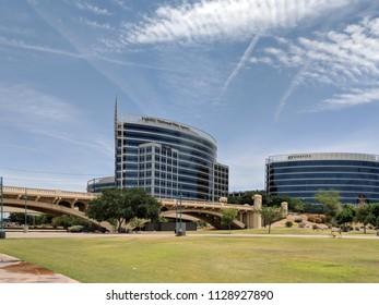 TEMPE, AZ, USA - MAY 21 2018:  Mill avenue bridge and office buildings in Neil G Guliano park at Sail River Lake, Tempe, AZ.