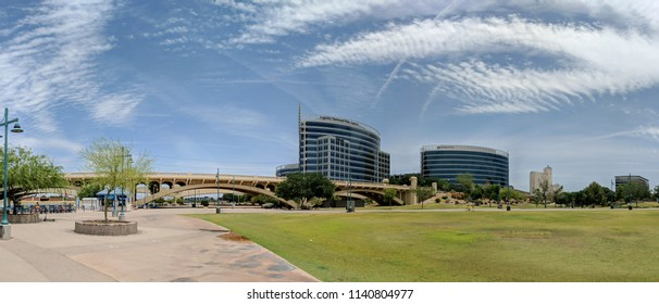 TEMPE, AZ, USA - MAY 21 2018:  Mill avenue bridge and office buildings in Neil G Guliano park at Sail River Lake, Tempe, AZ.