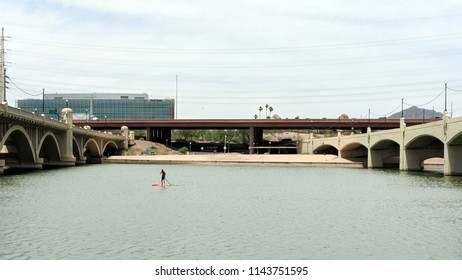 TEMPE, AZ, USA - MAY 21 2018:  Sportsman paddling between Mill Avenue bridges at Sail River Lake, Tempe, AZ.