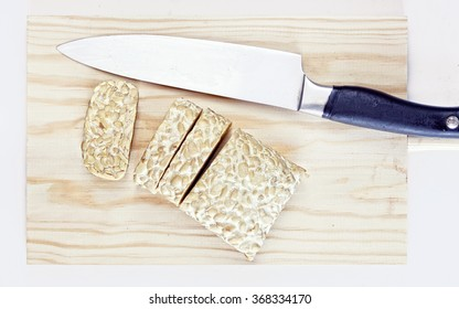 Tempeh on a wooden board with a knife
