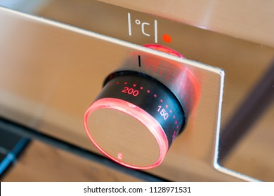 The Temperature Control On Kitchen Oven With Red Lighting Is Set To 200 Degrees Celsius