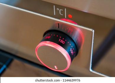 The temperature control on the kitchen oven with red lighting is set to 170 degrees Celsius. Close up view.