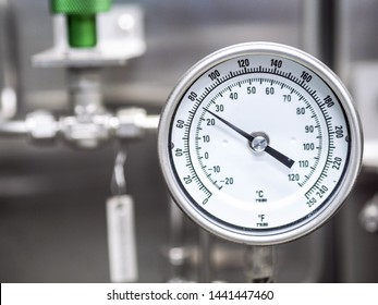 Temperature gauge for measuring instrument close up in industry zone at power plant.